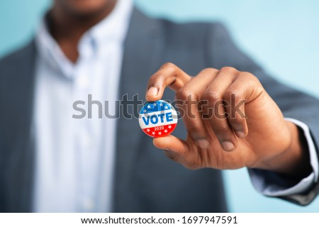African man holding vote button on blue background for the November elections in the United States 2020, blurred #1697947591