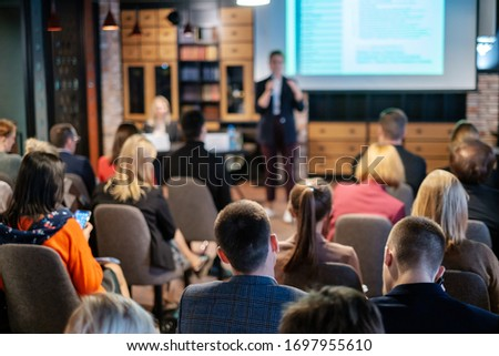 Audience listens lecturer at workshop in conference hall Royalty-Free Stock Photo #1697955610