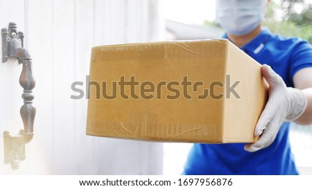 Delivery services courier during the Coronavirus (COVID-19) pandemic, close-up of cardboard box holding by a courier wearing protective face mask and latex gloves at home front door blurred background #1697956876