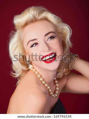 Pretty blond girl model like Marilyn Monroe on red background