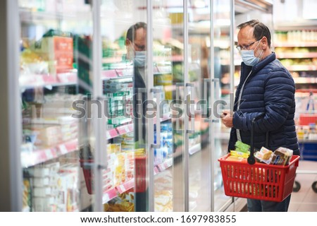 Middle age man buying food in grocery store, wearing medical mask Royalty-Free Stock Photo #1697983855