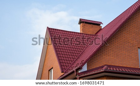 Red metal tile roof. Roof metal sheets. Modern types of roofing materials. Roof of the house, metal roof tile against the blue sky. Building. #1698031471