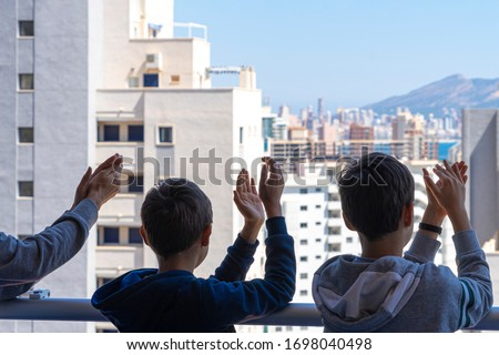 Family applauding medical staff from their balcony. People in Spain clapping gratitude on balconies and windows in support of health workers, doctors and nurses during the Coronavirus pandemic #1698040498