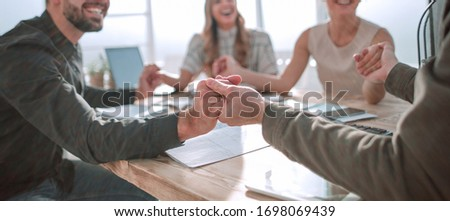 business team sitting at the table and showing their unity #1698069439