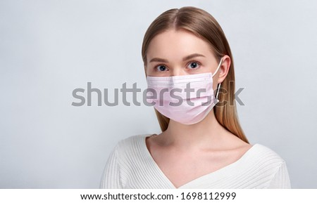 Studio portrait of young woman wearing a face mask, looking at camera, close up, isolated on gray background. Flu epidemic, dust allergy, protection against virus. Blonde woman #1698112999