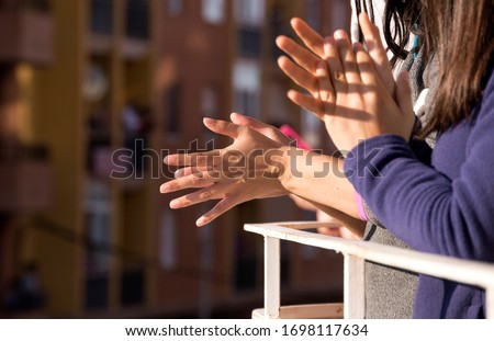 Woman hands applauding medical staff from their balcony. People in Spain clapping on balconies and windows in support of health workers, doctors during the Coronavirus pandemic. Selective Focus #1698117634