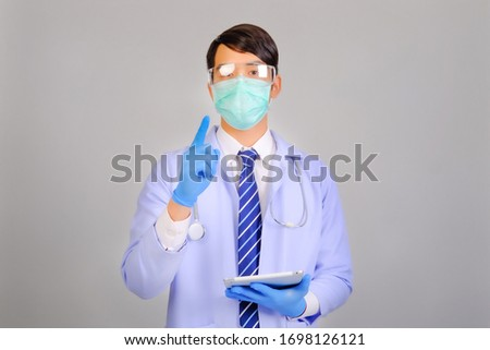 Medical doctor in white uniform doctor wears medical gloves, medical masks and and wearing protective glasses holding tablet on gray background, corona virus concept, covid19 concept, medical concept