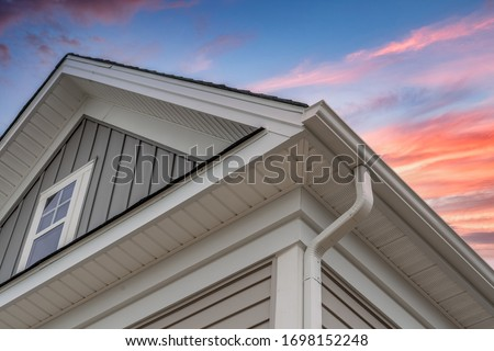 White frame gutter guard system, with gray horizontal and vertical vinyl siding fascia, drip edge, soffit, on a pitched roof attic at a luxury American single family home dramatic sunset sky #1698152248
