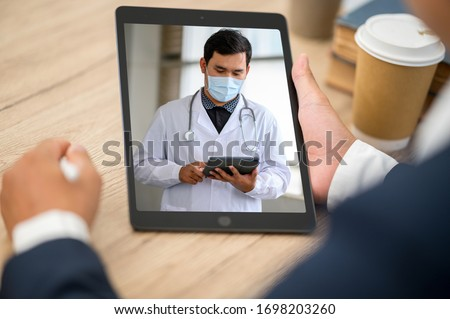 Close up of Business man sit at home having online consultation with doctor on Tablet,To reduce social distance healthcare concept #1698203260