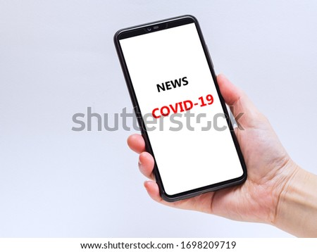 Covid 19 virus news on mobile, Mobile phone on hand with clipping path #1698209719