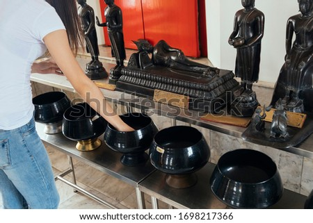 Cropped image of woman's hand drop the coin in the monk's alms-bowl on the table in front of Buddha statue.