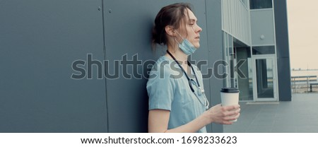 Portrait of tired exhausted nurse or doctor having a coffee break outside in the morning. COVID-19, Coronavirus pandemic #1698233623