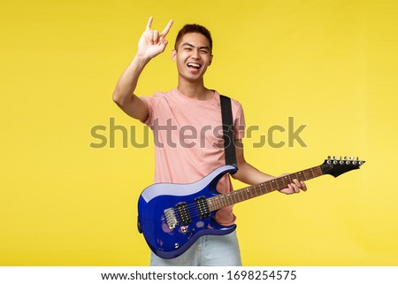 Lifestyle, leisure and youth concept. Happy carefree, good-looking asian guy playing in band, hold electric guitar, show rock-n-roll heavy metal sign and smiling broadly, perform on stage #1698254575
