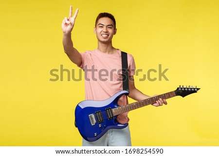 Lifestyle, leisure and youth concept. Peace my friends. Portrait of enthusiastic handsome asian guy playing on stage, performing song, holding electric guitar, invite listen to his band #1698254590