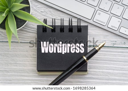 WORDPRESS text with decorative flower, keyboard, notepad and fountain pen on wooden background. Business and technology concept