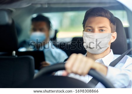 health protection, safety and pandemic concept - male taxi driver wearing face protective medical mask driving car with passenger #1698308866