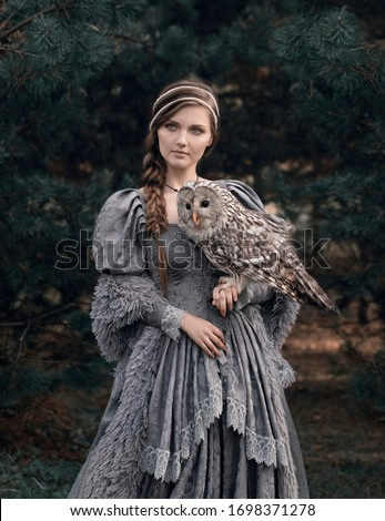 Art photo of a fairy-tale girl with a braid and an owl in her arms close up