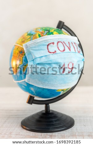 globe of planet dressed a medical mask with text Covid -19 worldwide epidemic. Coronavirus and quarantine planet infection pandemic concept