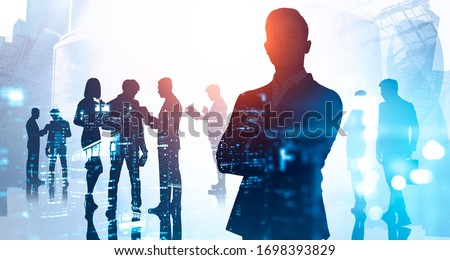 Silhouette of confident businessman standing with crossed arms in abstract city with double exposure of his blurry business team. Concept of leadership. Toned image #1698393829