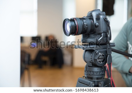 Camera to recording video live streaming at home . Focus on tripod mounted camera screen showing . Photo camera set on a tripod with excellent clipping path . Professional production photo camera. #1698438613