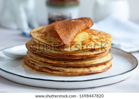 Fresh baked french crepes or Russians blinis on beautiful plate. Royalty-Free Stock Photo #1698447820