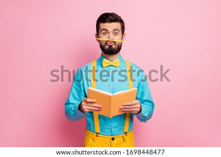 Portrait of his he nice attractive comic humorous cheerful bearded guy wearing mint shirt grimacing holding in hands diary pout lips isolated on pastel pink color background