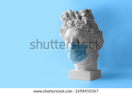 White plaster statue of the head of Apollo Belvedere in a medical protective mask. The concept Museum is closed for quarantine. Royalty-Free Stock Photo #1698450367