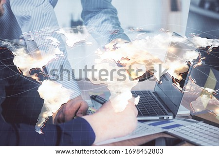 Double exposure of businessman working on laptop on background. International business hologram in front. Concept of success. #1698452803