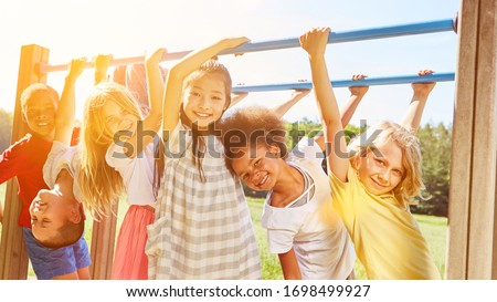 Group of children plays together at climbing frame on a playground in the summer Royalty-Free Stock Photo #1698499927