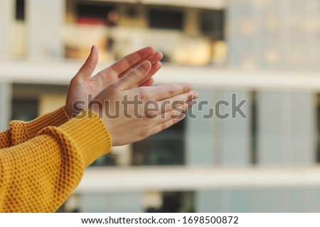 Stock photo of a close-up of hands clapping from the balcony in support of the medical team fighting against the coronavirus Royalty-Free Stock Photo #1698500872