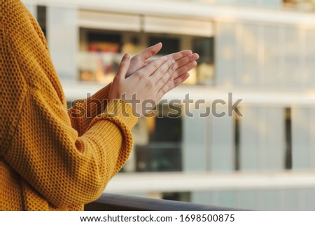 Stock photo of a girl's hands applauding from her balcony to support those fighting coronavirus #1698500875