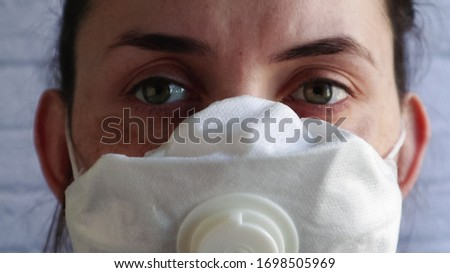 Close up of a female doctor blinking her eyes. Macro view, woman face in medical protective mask. Be safe. Portrait of a young woman against a white brick wall in a hospital or home setting. #1698505969
