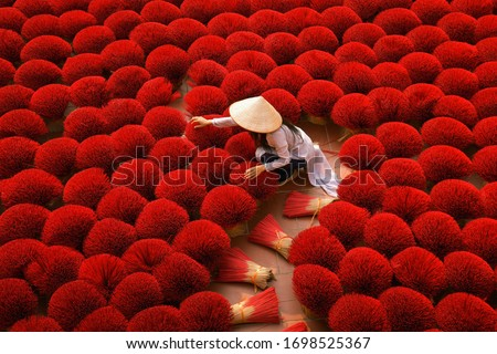 Incense sticks drying outdoor with Vietnamese woman wearing conical hat in Hanoi, Vietnam Royalty-Free Stock Photo #1698525367