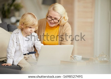 Senior woman in eyeglasses using laptop and teaching her grandson some online exercises at home #1698527491