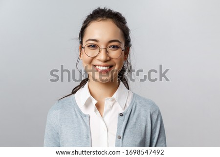 Close-up portrait of attractive, friendly-looking asian female office worker, employee or teacher in glasses, smiling broadly camera with enthusiastic attitude, stand grey background #1698547492