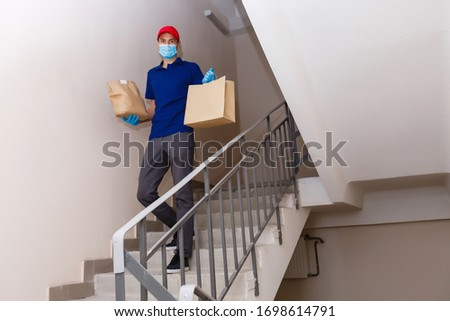 Delivery man holding paper bag with food on white entrance of house background , food delivery man in protective mask #1698614791