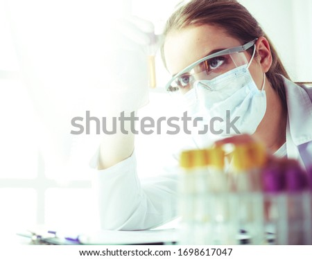 Portrait of pretty female laboratory assistant analyzing a blood sample at hospital #1698617047