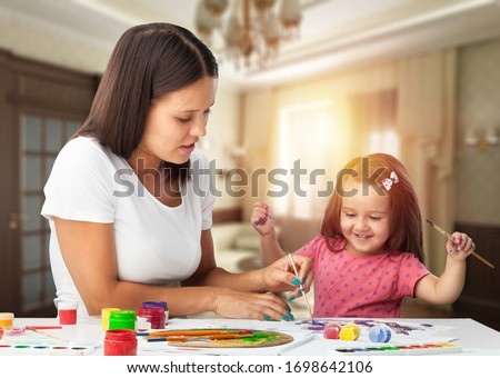 Beautiful mommy and her kid paintig a picture at home