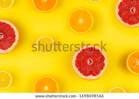 Pattern with sliced grapefruit, orange, lemon flat lay on colorful yellow background top view copy space. Summer, holidays, vacation concept. Fruit creative layout web banner template. Stock photo.