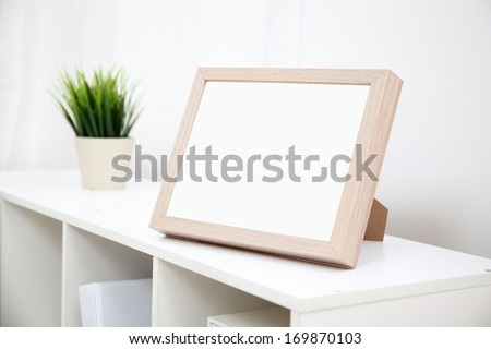 blank photo frame with copy space on white bookshelf at home