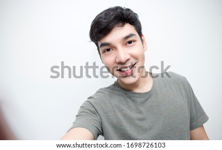 Portrait of young handsome asian man use smartphone selfie say hi over white background. Happy asian guy online influencer blogger. Education technology connected people man lifestyle concept