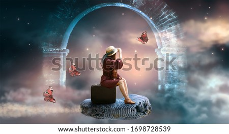 Young lady woman in retro dress and hat sitting on suitcase and flies on ammonite fossil through space and universe, idyllic fantasy scene with ghost arch ruins and butterflies, travel around world. Royalty-Free Stock Photo #1698728539