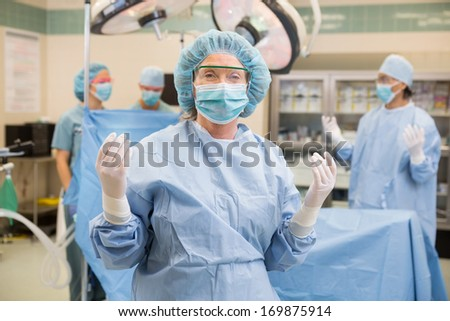 Mature female doctor in surgical gown with team standing at operation room #169875914