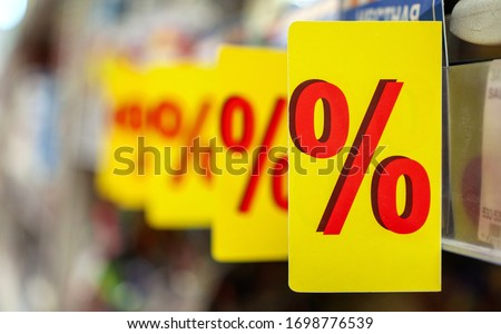 """Sign of """"%"""" wording at consumer good's shelf in the supermarket. """"%"""" label (tag), symbol of special promotion as concept of offering product at reduced price. Shelves in blurry for background."""