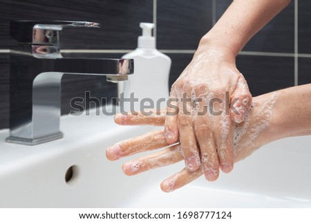 Woman washing hands with soap. An unrecognizable female showing how to wash hands properly. Coronavirus or COVID-19 prevention #1698777124