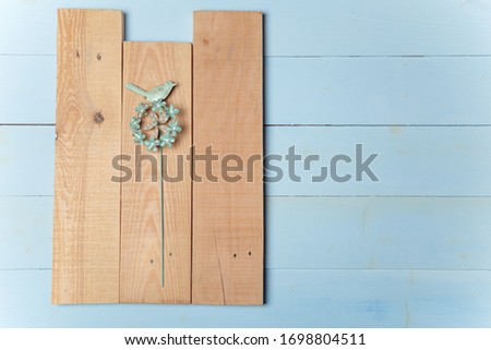 Tender pinwheel with bird and flowers on brown boards lying on wooden blue background. Spring nestlings, springtime and Easter concept. Flatlay, place for text. #1698804511
