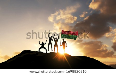 A group of people celebrate on a mountain top with Burkina Faso flag. 3D Render #1698820810