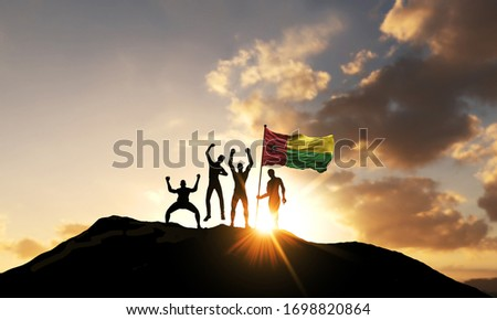 A group of people celebrate on a mountain top with Guinea Bissau flag. 3D Render #1698820864