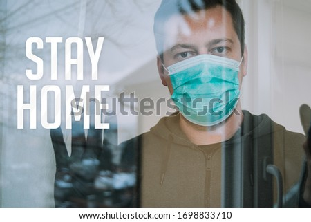 young man in isolation looking trough window with mask and gloves in isolation protecting from coronavirus covid-19 with text stay home #1698833710