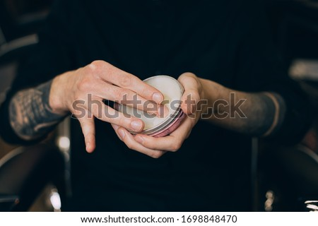 balm-wax. beard oils. barber shop beard care.jar with wax in the hands of a barbershop Royalty-Free Stock Photo #1698848470
